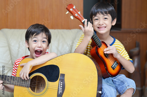 little sibling boy playing guitar and ukulele happy face