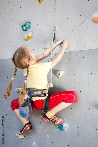 teenager climbing a rock wall