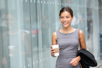 Business woman walking drinking coffee