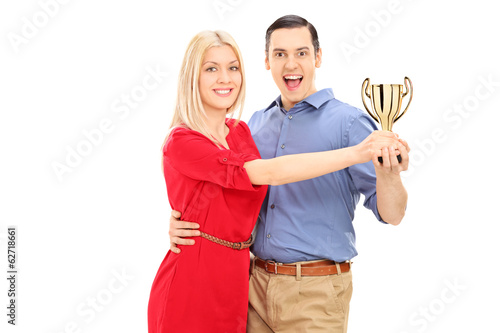 Young couple holding a trophy