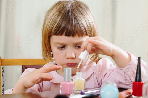 three year old girl making manicure
