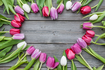 Frame of fresh tulips arranged on old wooden background