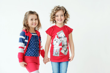 Two cute little girls talking on a white background.