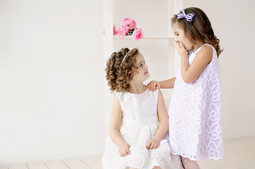 Cute little girls in white dresses talking.