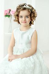 Cute little girl in white dresse.
