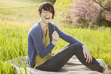 A Young Woman Sitting In An Open Space, A Grass Field, On A Blanket.