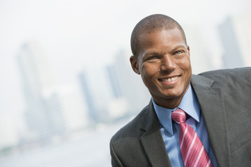 A Young Man In A Business Suit With A Blue Shirt And Red Tie. On A City Street. Smiling At The Camera.