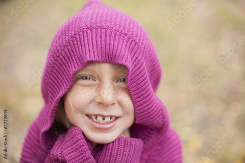 A Girl In A Magenta Hooded Sweater, With The Hood Covering Her Head