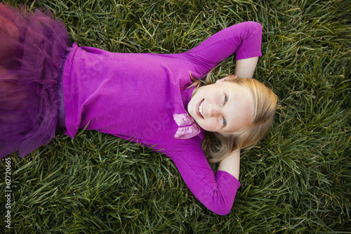 A Young Girl Lying On Her Back On The Grass, With Her Hands Behind Her Head, Smiling And Looking At The Camera. View From Above.