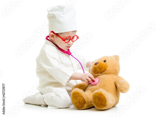 Adorable child with clothes of doctor playing with toy