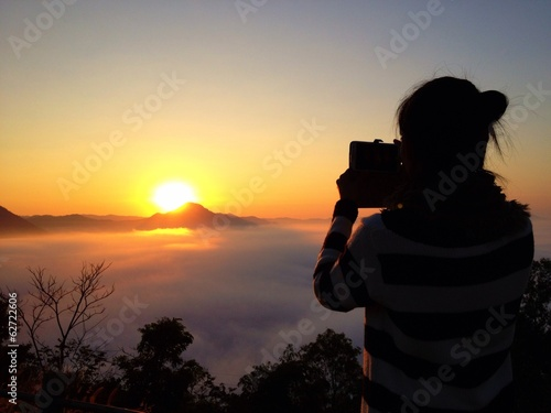 Woman silhouette take mobile photo of sunrise