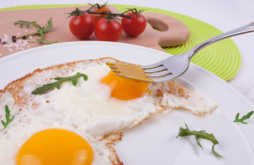 Fried eggs with arugula leaves and cherry tomatoes