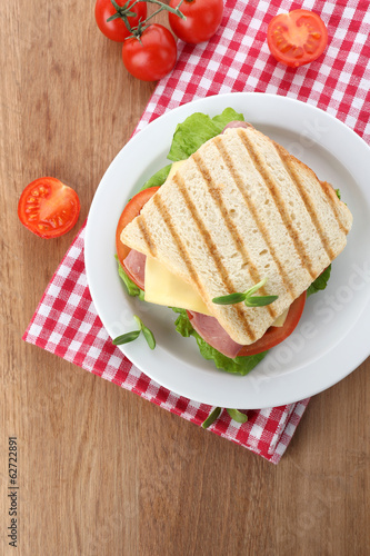 Tasty sandwich with ham on wooden table