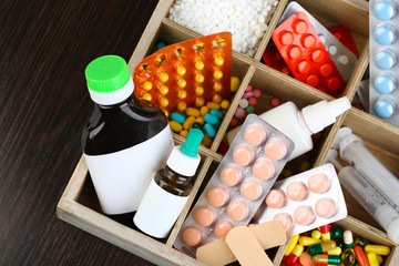 Medical pills, ampules in wooden box, on color wooden