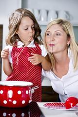 Deutschland, Mutter und Tochter essen Nudeln in der Küche