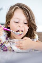 Deutschland, Mädchen essen Müsli in der Küche