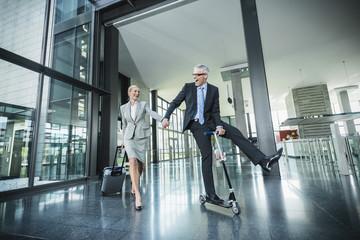 Deutschland, Stuttgart, Geschäftsfrau mit Rollkoffer, Mann auf Roller auf Bürogebäude