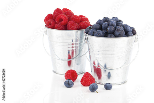 blueberry and raspberries berries in a metal bucket, isolated on