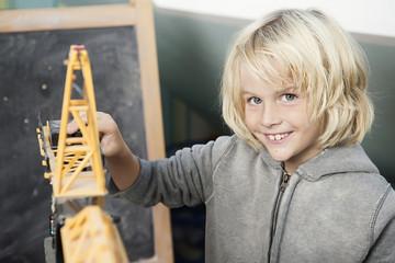 Blonder Junge mit Spielzeugkran