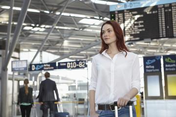 Deutschland, Köln, junge Frau mit Gepäck am Flughafen
