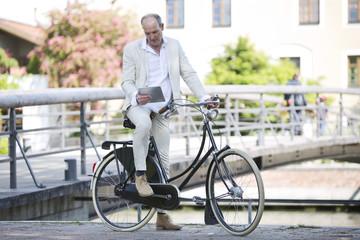 Deutschland, Bayern, Mann mit dem Fahrrad und mit Tablet PC