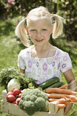 Deutschland, Bayern, Mädchen halten Gemüsekiste