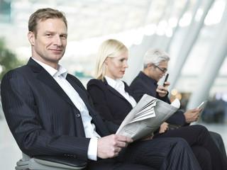 Geschäftsleute und Frau am Flughafen warten