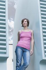 Deutschland, Bonn, Frau lehnt an Gebäude
