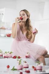 Deutschland, Junge Frau beisst Erdbeere, Gläser mit Erdbeer-Joghurt