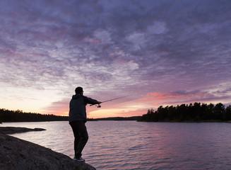 Schweden, Junger Mann Angeln bei Sonnenuntergang