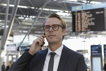 Deutschland, Köln, Mann am Telefon sprechen am Flughafen