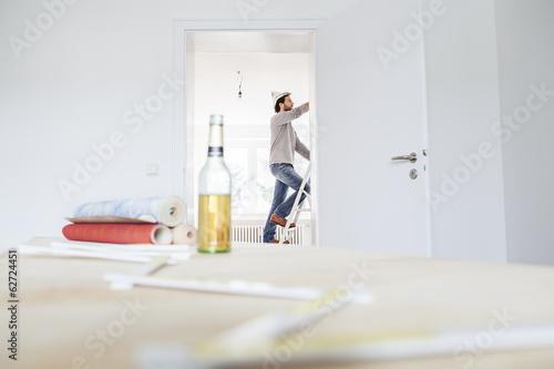 Mann steht auf Stufenleiter, Tapeten und Bierflasche im Vordergrund