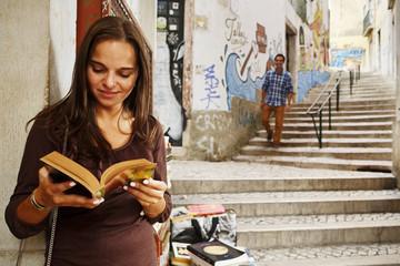 Portugal, Lissabon, Baixa, Rua do Madalena, junge Frau mit Buch stand vor der antiquarische Buchhandlung