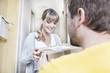 Deutschland, Köln, Junge Frau, die Pizza-Box ab Lieferung Mann lächelnd