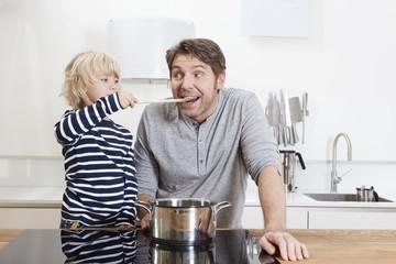 Deutschland, München, Sohn gibt Vater essen in der Küche
