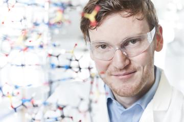 Deutschland, junger Wissenschaftler mit DNA-Modell