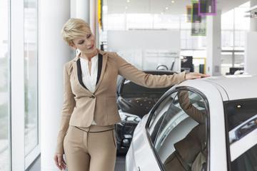 Beim Autohändler, Frau, die am neuen Auto steht