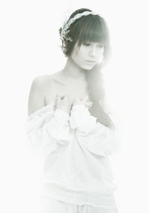 Junge Frau im weißen Kleid vor weißem Hintergrund