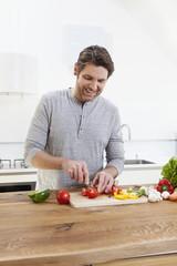 Deutschland, München, Mann schneidet Gemüse in der Küche