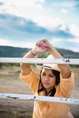 USA, Texas, Junge Frau lehnt am Zaun