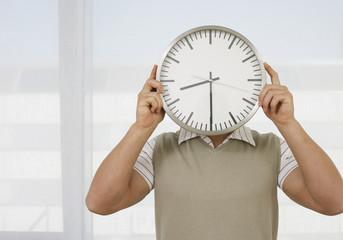 Junger Mann hält Uhr vor Kopf