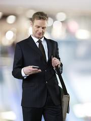 Geschäftsmann mit Schultertasche mit Smartphone