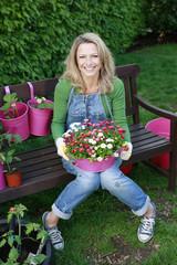 Deutschland, Bayern, Frau sitzt auf der Bank mit Topfpflanze