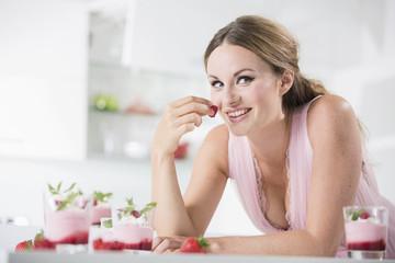 Deutschland, Junge Frau mit Erdbeere