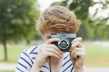 Junger Mann, fotografiert im Park mit einem altmodischen Kamera