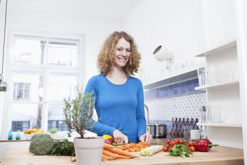 Deutschland, München, junge Frau schneidet Gemüse in der Küche
