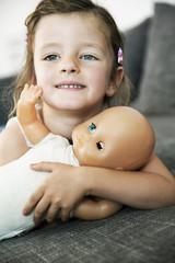 Mädchen auf dem Sofa mit ihrer Puppe liegend