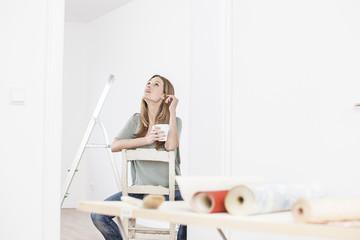 Frau sitzt auf dem Stuhl mit Tasse