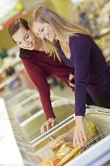 Deutschland, Köln, Junge Frauen am Gefrierfach im Supermarkt
