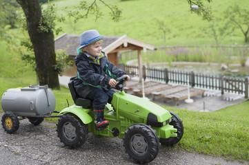 Deutschland, Bayern, Junge sitzt im Spielzeug-Traktor mit Anhänger